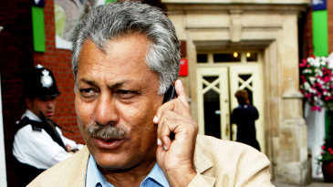 Zaheer Abbas talks on the phone as he walks towards the team bus at The Oval