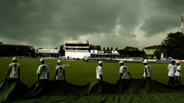 The groundstaff prepare to bring the covers on