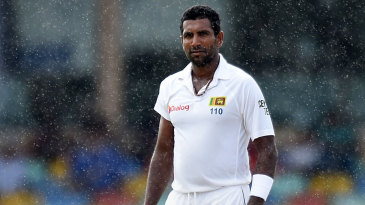 Dhammika Prasad looks on amidst the rain