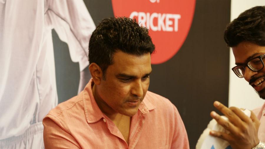 Former India batsman Sanjay Manjrekar signs an autograph at the event