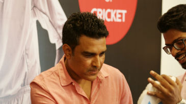 Former India batsman Sanjay Manjrekar signs an autograph at the event
