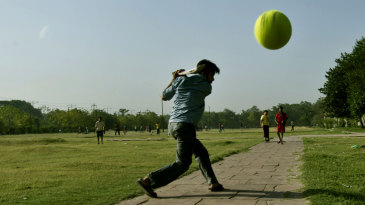 Kids play cricket in a park in New Delhi