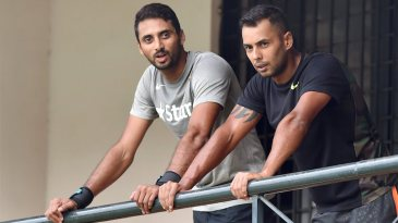 Karnataka team-mates S Aravind and Stuart Binny look on from the balcony