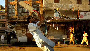 Pakistani men and boys play tape-ball cricket in the streets of Rawalpindi