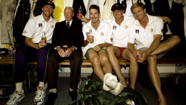 Invincible Bill Brown shares a beer with Australian players in the dressing room in Hobart