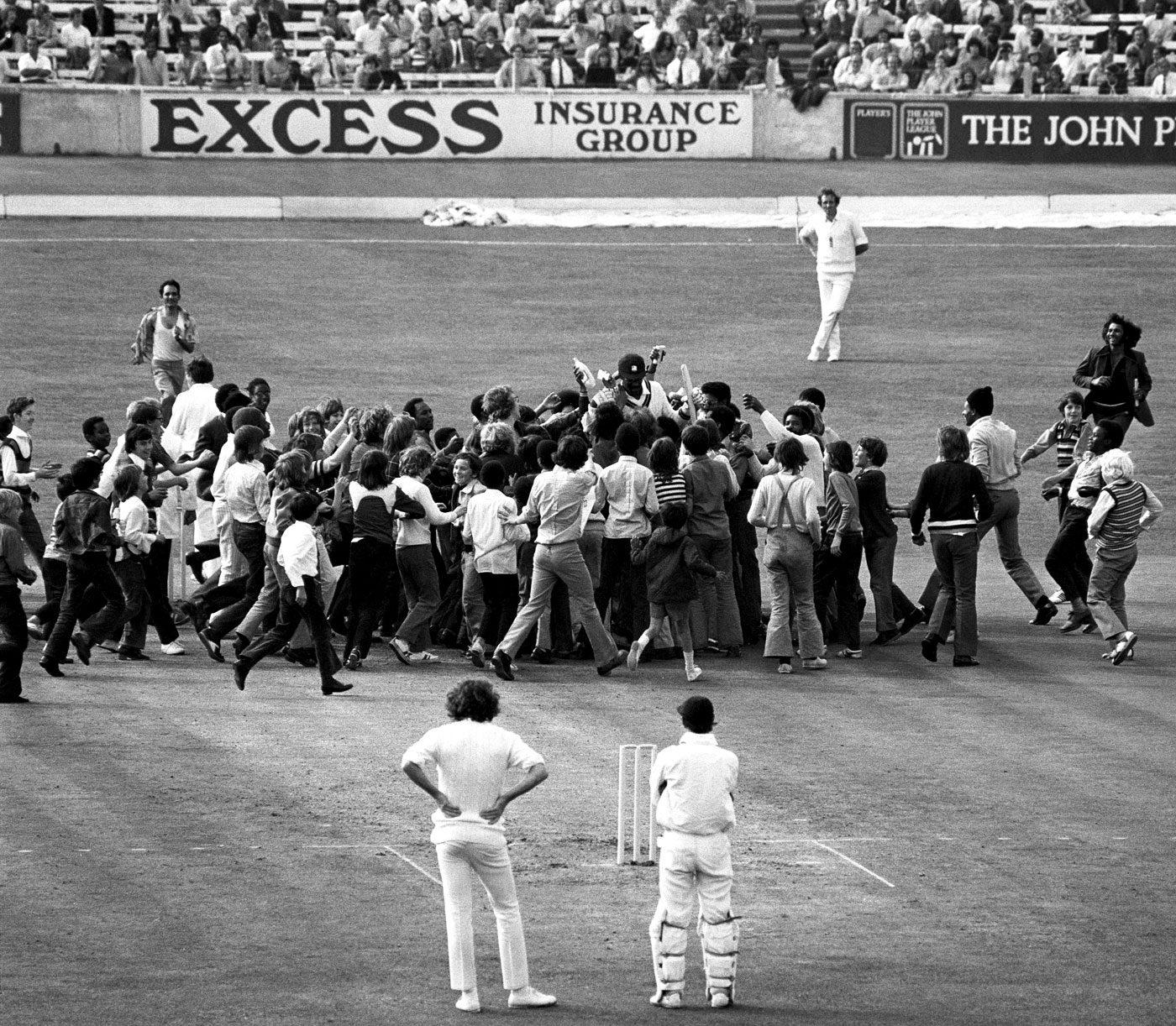 The English players can only watch as Clive Lloyd is engulfed by fans after his making a century at the Oval on the first day of the first Test in 1973