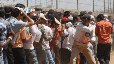 A policeman lathicharges fans queuing up outside the stadium in Motera
