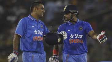 MS Dhoni and Suresh Raina chat during their fifth-wicket stand