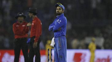 Virat Kohli waits during a crowd interruption