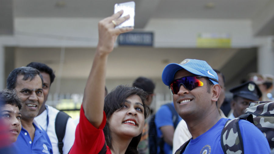 A fan clicks a selfie with MS Dhoni