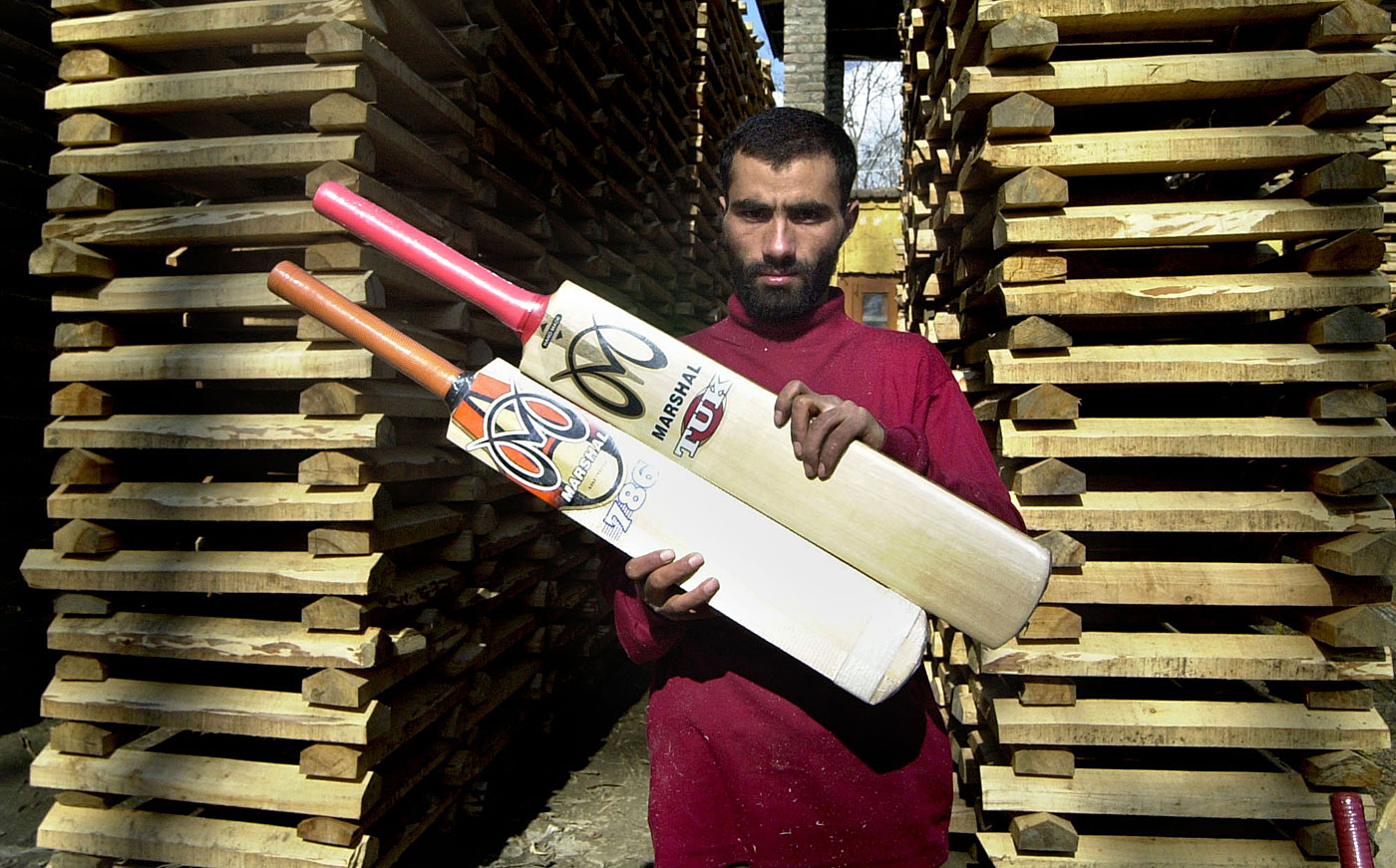 A worker holds two cricket bats at a bat-making factory in Awantipora