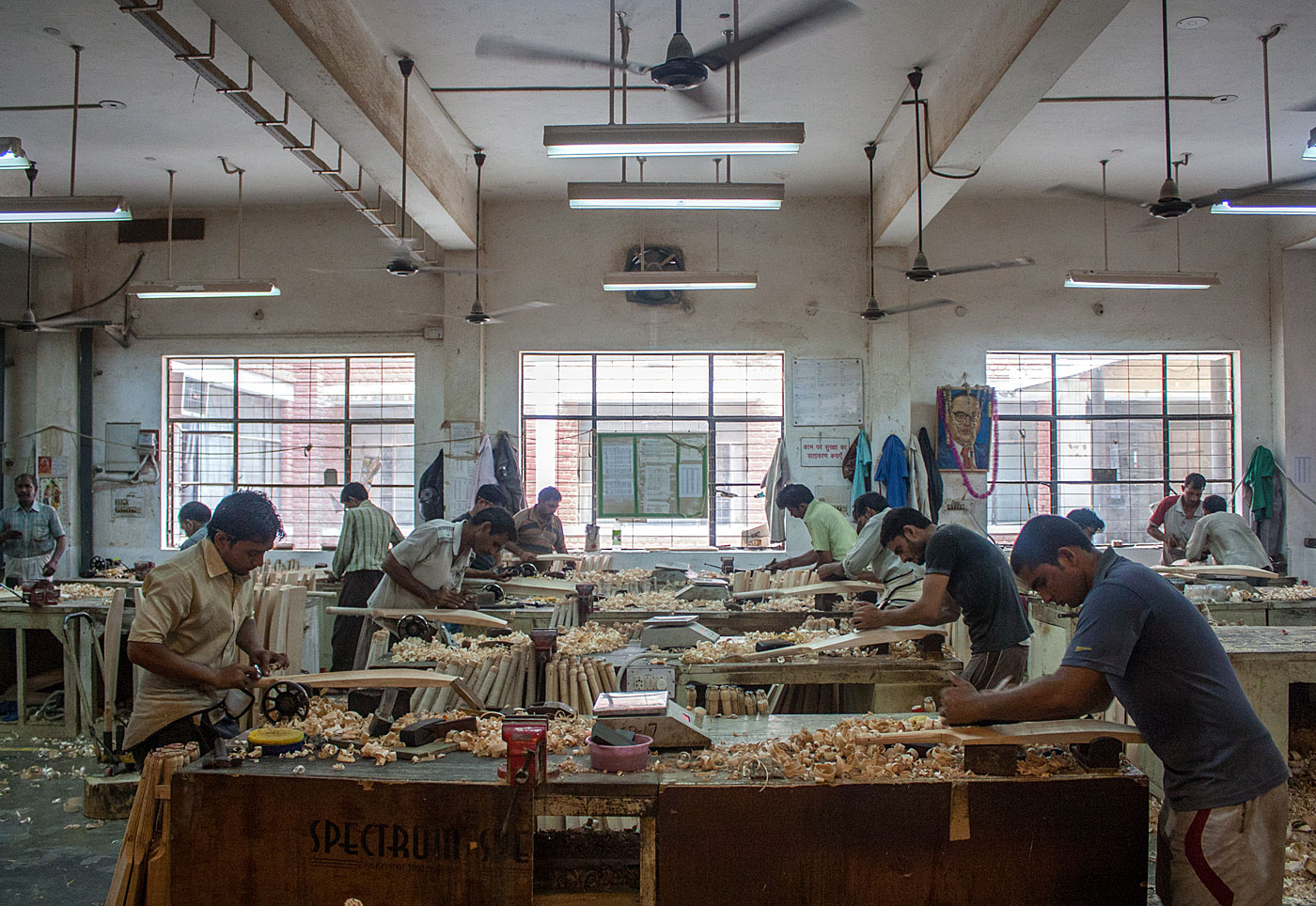 Workers handcraft bats on the SG factory shop floor