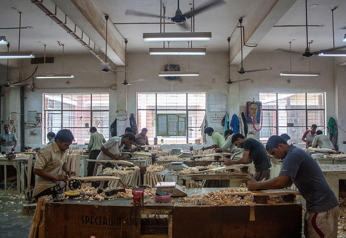 Workers handcraft bats on the SG factory shop floor