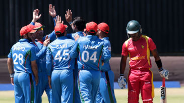 Dawlat Zadran is mobbed by his team-mates after dismissing Chamu Chibhabha