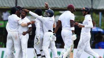 The Sri Lankans rush to celebrate with Rangana Herath