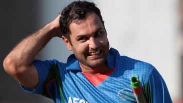 A smiling Mohammad Nabi walks back after steering Afghanistan to victory