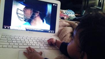 A child watches Sachin Tendulkar on a computer screen