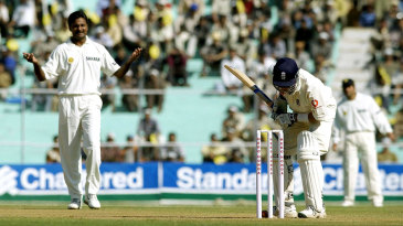 Javagal Srinath looks on as Craig White tries to prevent the ball from hitting the stumps
