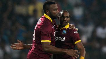 Kieron Pollard congratulates Dwayne Bravo after the latter took a wicket