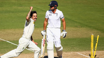 Mitchell Johnson celebrates as a shell-shocked Alastair Cook looks on