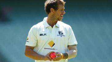 James Pattinson walks back to his mark with the pink ball