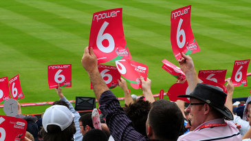 Fans celebrate a six by holding placards