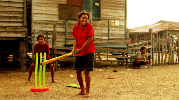 A girl from the village of Hanuabada bats during a game of cricket in the streets in Port Moresby, Papua New Guinea