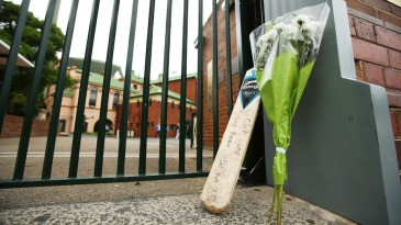 A bat and a bouquet left outside the SCG in tribute to Phillip Hughes