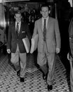 Jackie McGlew and Sid O'Linn walk out of a tailoring store in their new suits, London, September 10, 1960