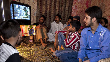 Fans in a Karachi house watch a cricket match on television