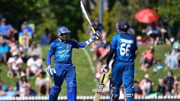 Tillakaratne Dilshan raises his bat after reaching his fifty