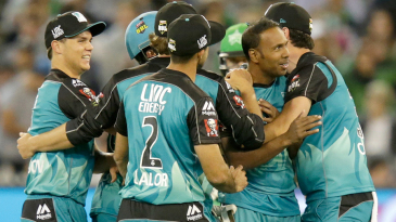 Samuel Badree is mobbed by team-mates after taking a wicket