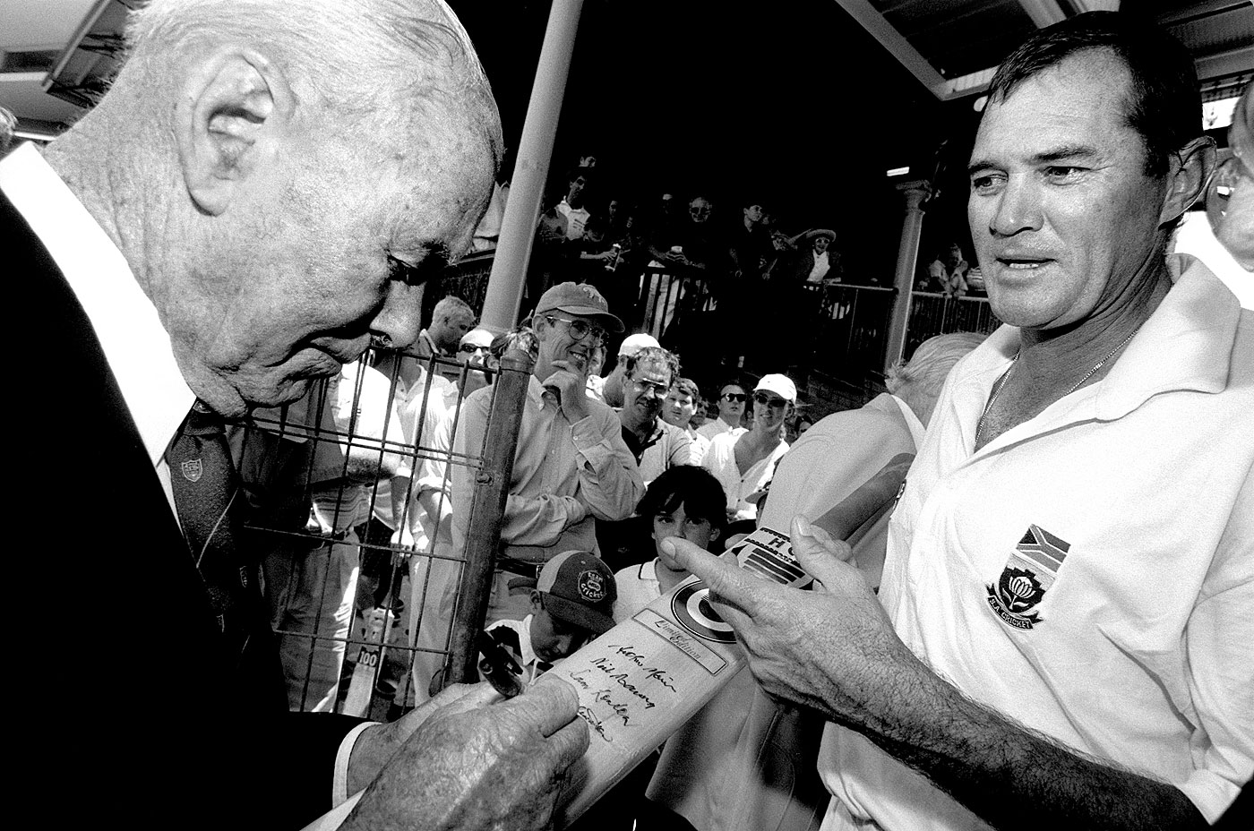 Blessings from an Invincible: Bill Brown signs the bat of a man who become the only player ever to pass 50 in Tests batting at eight, nine, 10 and 11