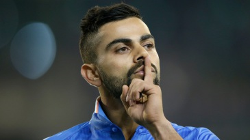 Virat Kohli gestures to the crowd while fielding