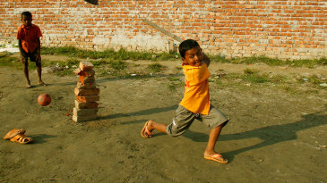 Boys in Dhaka play cricket using a stack of bricks as stumps