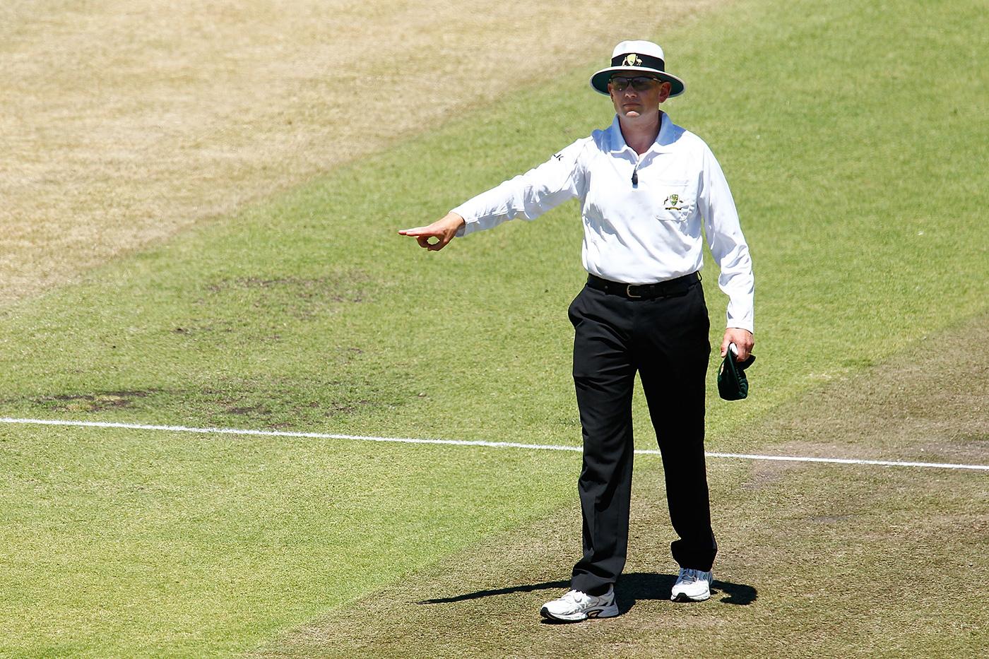 Umpire Sam Nogajski signals a four