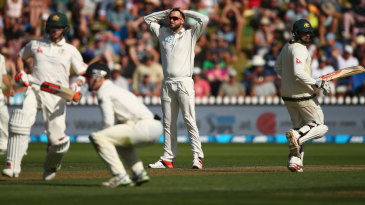 Mark Craig reacts to a chance as Steven Smith and Usman Khawaja complete a run