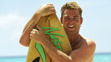 Shane Warne poses with a surfboard in the West Indies