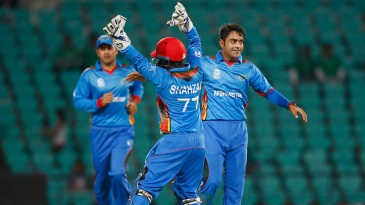 Rashid Khan (R) and Mohammad Shahzad celebrate the wicket of Richie Berrington