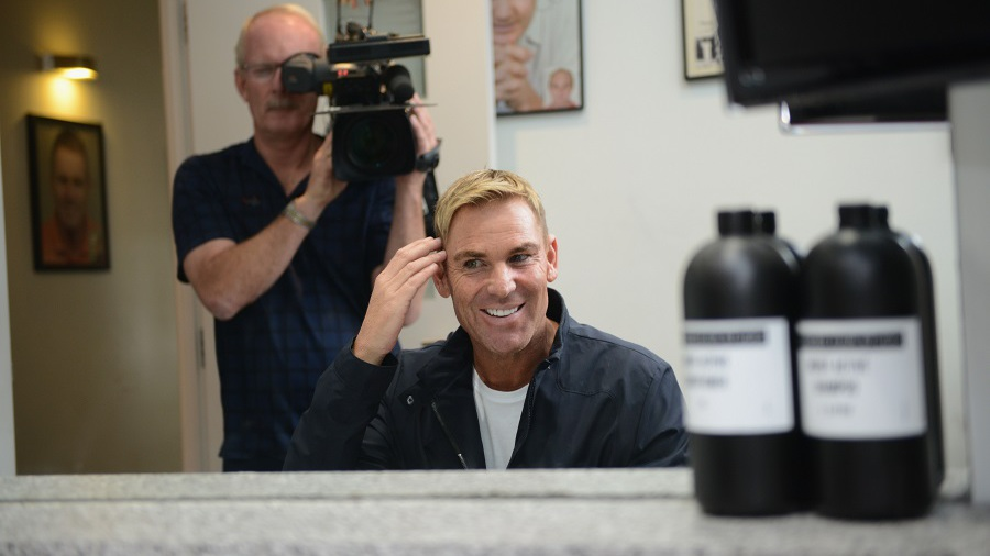 Shane Warne checks out his hairdo at a promotional event in Melbourne