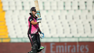 Suzie Bates raises her bat after reaching her 13th T20I fifty