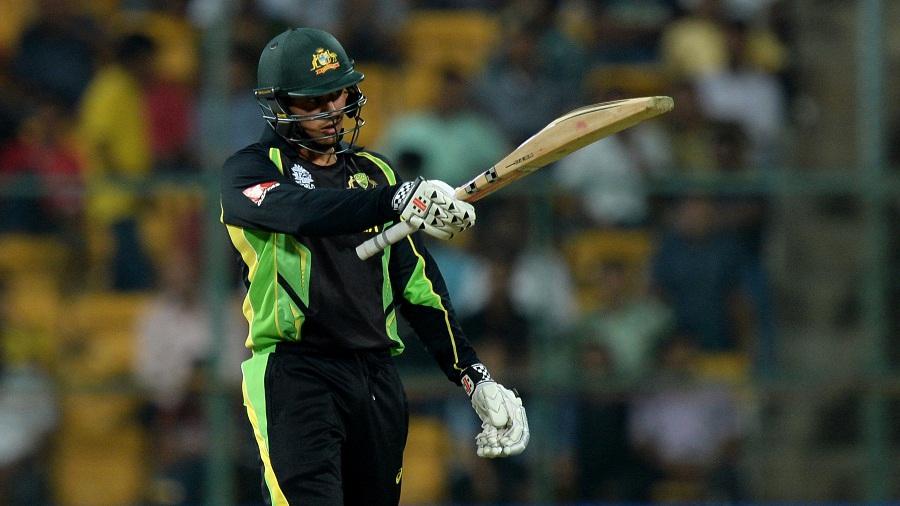 Usman Khawaja raises his bat after reaching his fifty