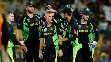 Adam Zampa is mobbed by his team-mates after picking up a wicket