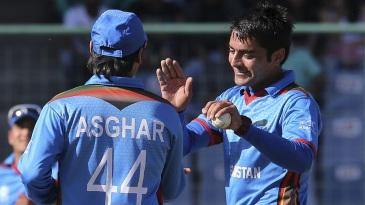 Rashid Khan celebrates a wicket with Asghar Stanikzai