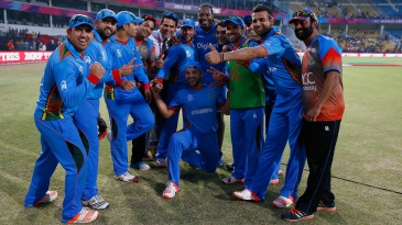 Chris Gayle poses with the Afghanistan players after the match