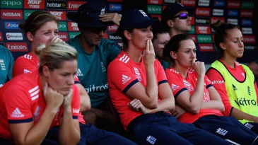 A disappointed England team looks on from the dugout after being defeated