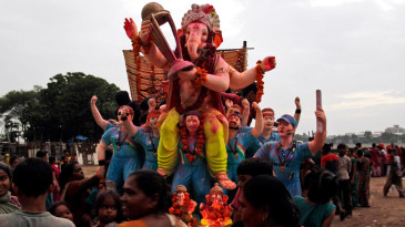 An idol of the Hindu god Ganesha, holding a World Cup, and flanked by Indian cricketers makes its way to the Sabarmati river for immersion