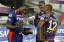 Carlos Brathwaite takes a look at Andre Russell's Player-of-the-Match award even as Jason Holder looks on, Kolkata Knight Riders v Delhi Daredevils, IPL 2016, Kolkata, April 10, 2016