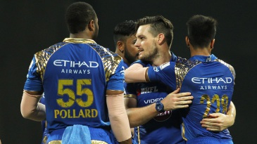 Mitchell McClenaghan is mobbed by his team-mates