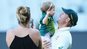David Warner plays with his daughter Ivy while his wife, Candice, takes a photo of them